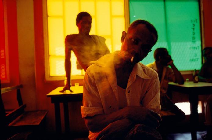 Un homme avec une cigarette nous regarde fixement dans un bar
