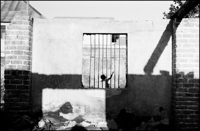 Alex Webb : Un enfant joue dans une maison dont le toit est détruit