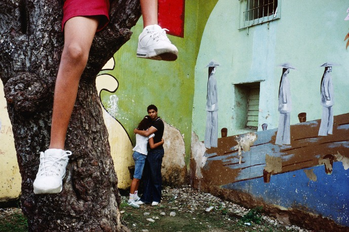 Alex Webb : Un enfant est assis sur une branche au-dessus d'un couple