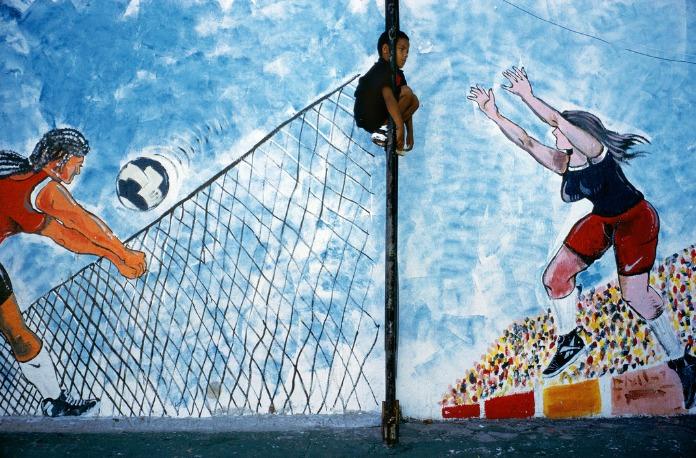Alex Webb : Un enfant grimpe en haut d'un poteau