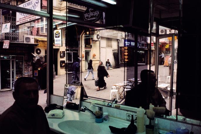 Alex Webb : Un homme est assis dans un salon de coiffure