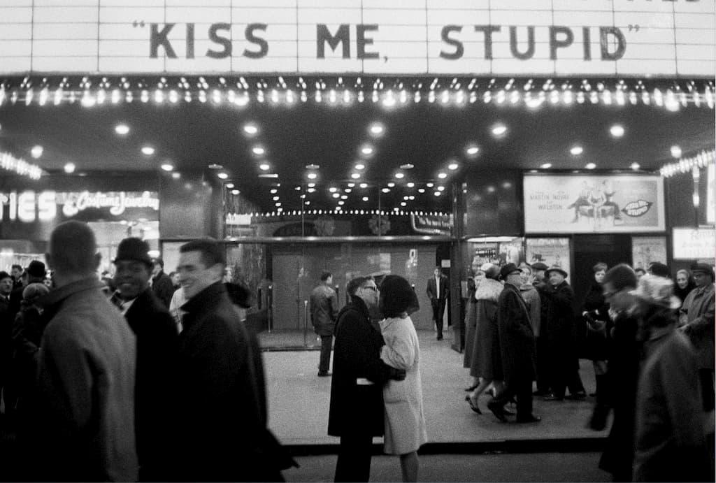 un couple s'embrasse devant un cinéma