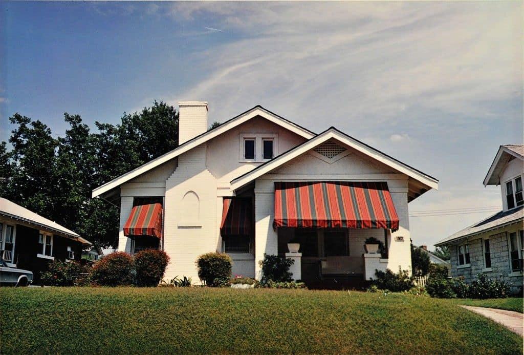 maison avec stores rouges et pelouse verte