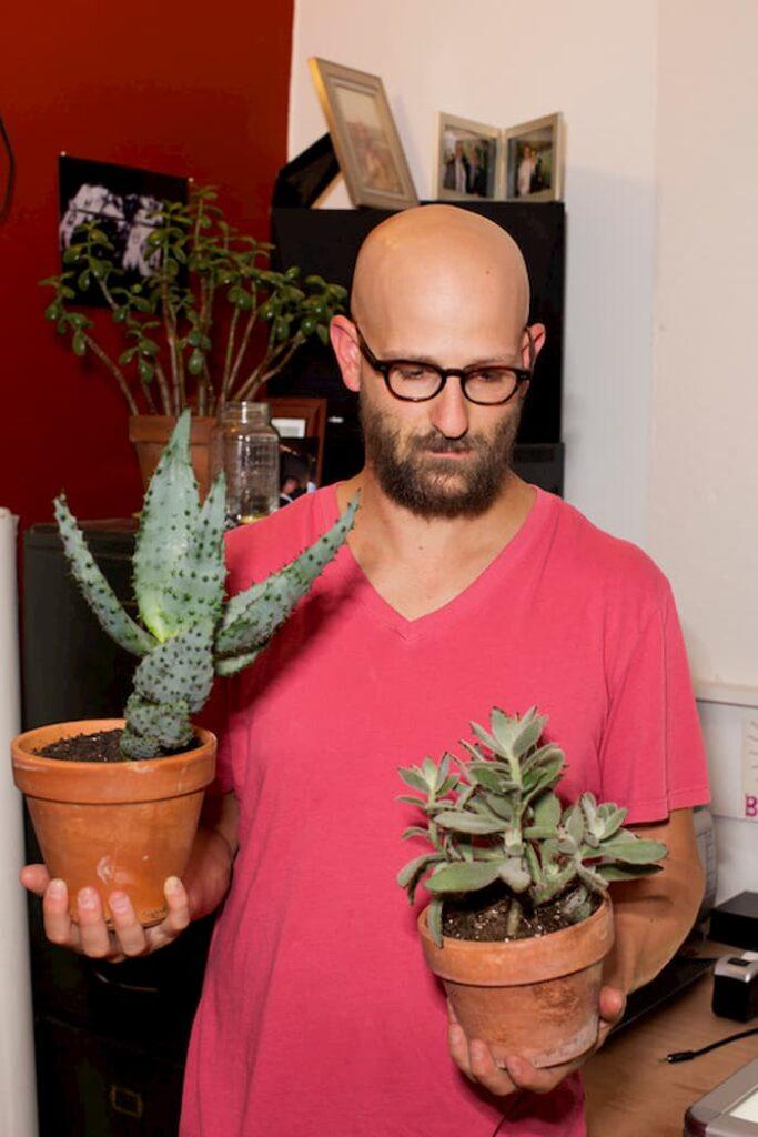 Portrait de Gregory Halpern avec deux plantes