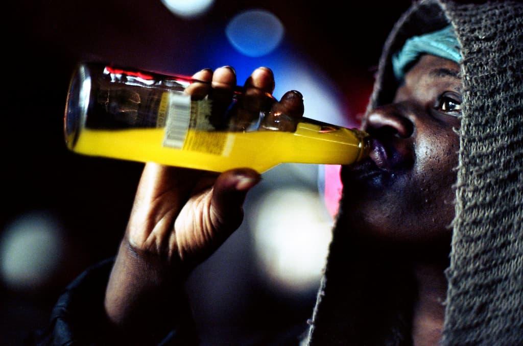 Photo de Khalik Allah : un homme boit dans une bouteille fluorescente