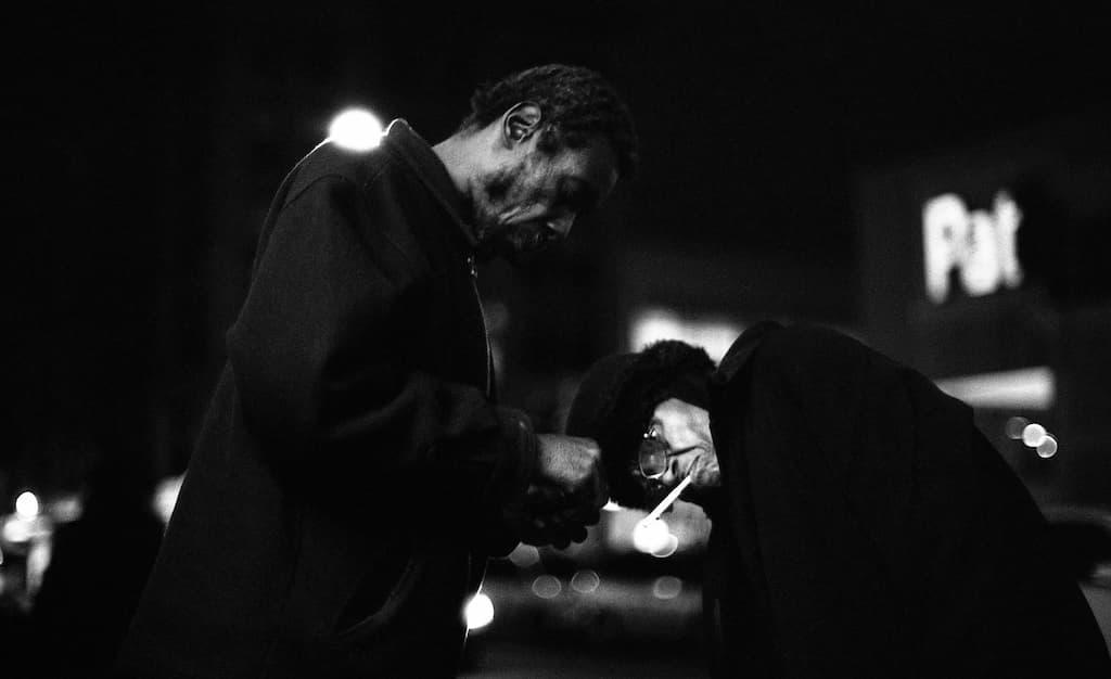 Photo de Khalik Allah : un homme allume la cigarette d'une seconde personne
