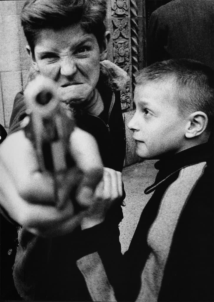 Un enfant vise le photographe avec un pistolet en plastique